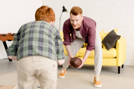 smiling red haired father and son playing with rugby ball at home