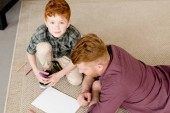 high angle view of cute little boy smiling at camera while drawing with father at home