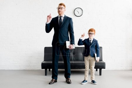 father and little son businessmen holding digital tablets and pointing up with fingers