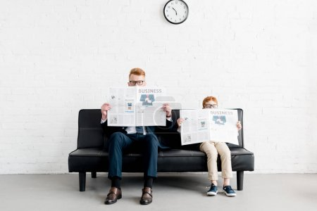 father and little son businessmen wearing eyeglasses and reading newspapers