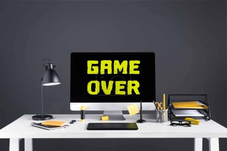 desktop computer with game over inscription on screen, graphics tablet and office supplies at workplace