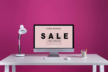 desktop computer with cyber monday sale inscription on screen, keyboard, computer mouse and office supplies on table