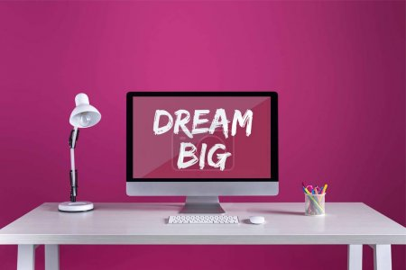desktop computer with dream big inscription on screen, keyboard, computer mouse and office supplies on table