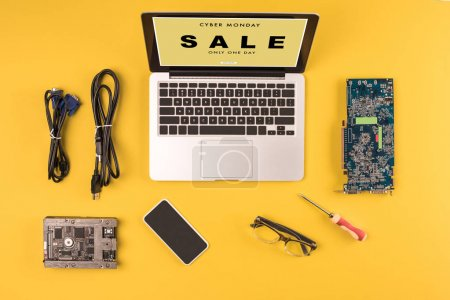 Photo for Top view of laptop with inscription cyber monday sale only one day, smartphone, eyeglasses and wires on yellow - Royalty Free Image