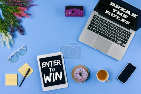 top view of digital devices with inscriptions enter to win and break the rules, flowers, cup of coffee with doughnut and camera on blue