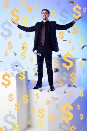 Photo pour Un homme d'affaires souriant en costume debout sur un bloc blanc avec des billets en dollars tombants et des symboles autour - image libre de droit