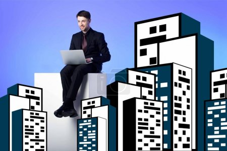 smiling businessman with laptop sitting on white block between drawing buildings on blue