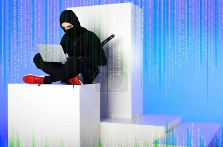 ninja in black clothing using laptop while sitting on white block with code on blue