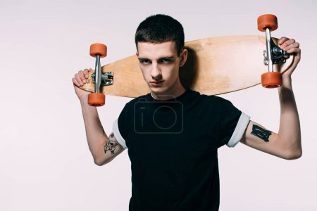 Hipster young guy holding longboard on shoulders isolated on white