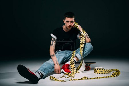 Photo for Hipster man sitting on longboard in yellow tape on dark background - Royalty Free Image