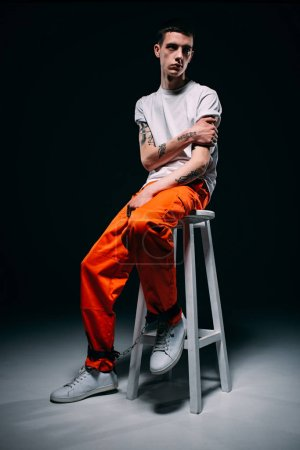 Photo for Man with tattoos wearing orange pants sitting on stool on dark background - Royalty Free Image