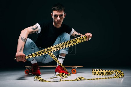 Photo for Young man sitting by longboard with police line in hands on dark background - Royalty Free Image