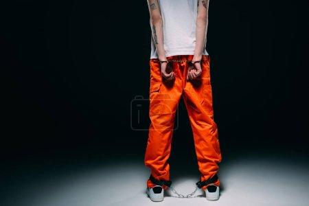 Photo pour Vue recadrée de l'homme portant l'uniforme de prison avec les mains menottées derrière le dos sur fond sombre - image libre de droit