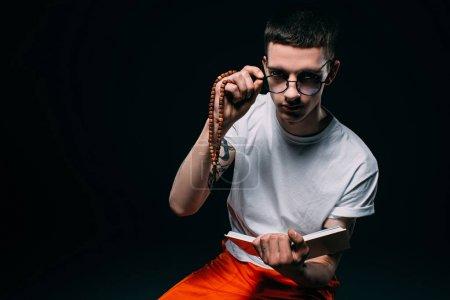 Photo pour Homme prisonnier tenant le chapelet et lecture bible sur fond foncé - image libre de droit