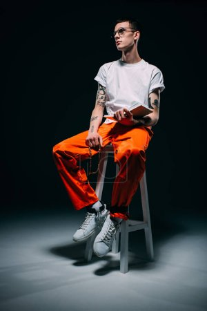 Man with tattoos wearing orange pants holding rosary and bible while sitting on stool on dark background