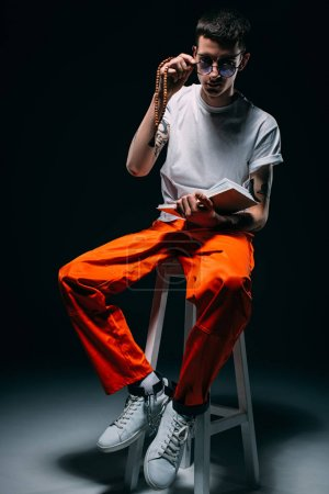 Man in orange uniform with cuffs on legs reading bible while sitting on stool on dark background