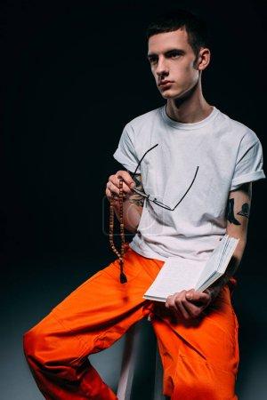 Thoughtful male prisoner holding bible on dark background