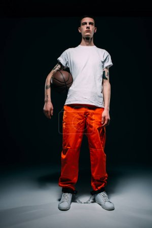 Photo for Young male prisoner wearing orange pants and cuffs holding basketball ball on dark background - Royalty Free Image