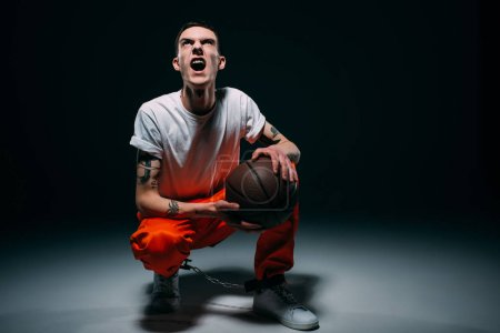 Photo for Screaming man in prison uniform and cuffs holding basketball ball on dark background - Royalty Free Image