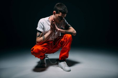 Photo for Sad male prisoner in orange pants and cuffs holding rosary and praying on dark background - Royalty Free Image