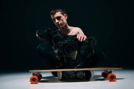 Black dog standing on longboard by its owner on dark background