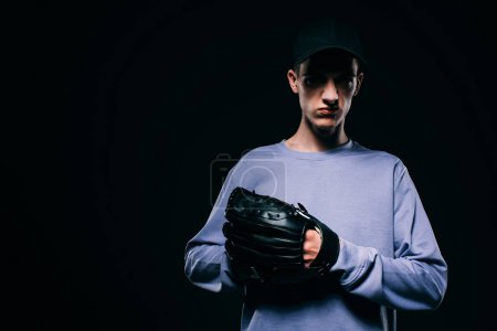 Man in baseball cap wearing baseball mitt isolated on black