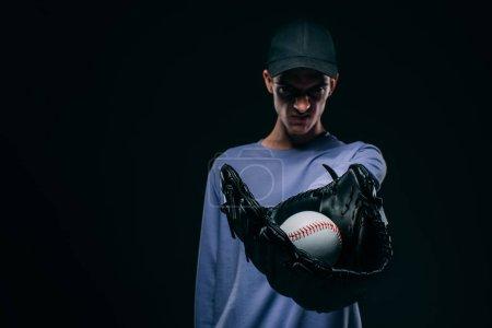 Angry man wearing baseball glove showing baseball ball isolated on black