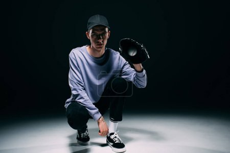 Handsome young man with baseball glove catching ball on dark background