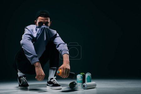 Man with covered face sitting by spray print cans on dark background