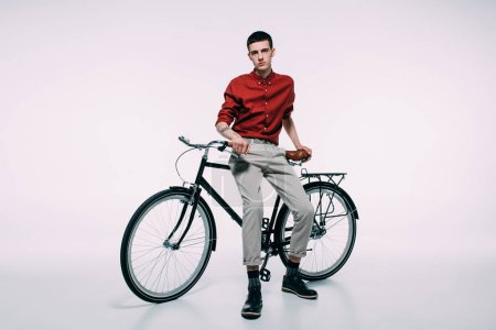 Hipster male cyclist leaning on his bike on white background