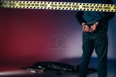 Rear view of murderer in cuffs behind police line on dark background