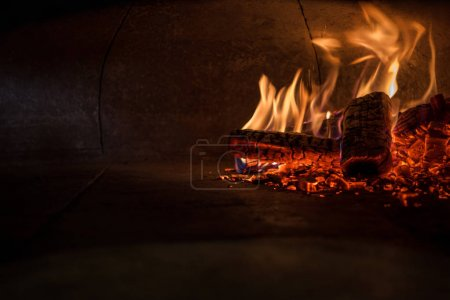 close up view of firewood in brick oven in restaurant