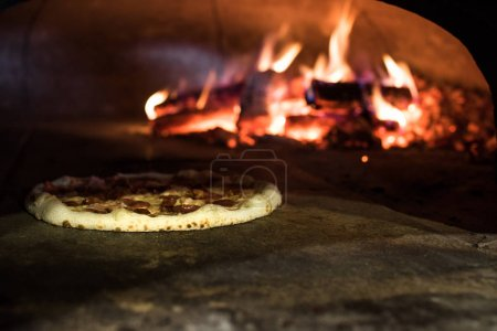 close up view of italian pizza baking in brick oven in restaurant