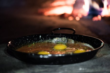 close up view of eggs in frying pan cooking in brick oven