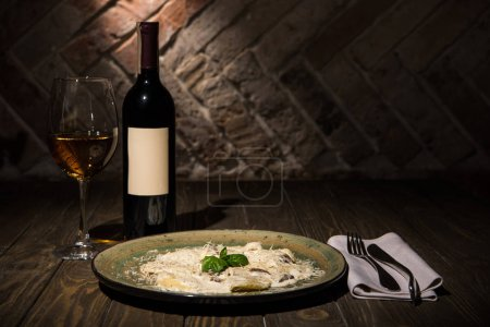 close up view of italian dish with cutlery and wine on wooden surface