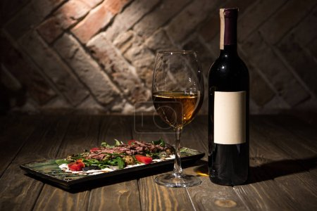 close up view of italian salad with bottle and glass of wine on wooden tabletop