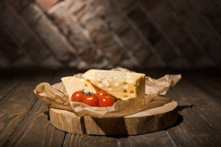 close up view of fresh cherry tomatoes and cheese on baking paper on wooden stump