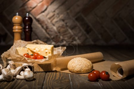 Photo for Close up view of fresh cherry tomatoes, cheese, mushrooms and loaf of bread on baking paper on wooden tabletop - Royalty Free Image