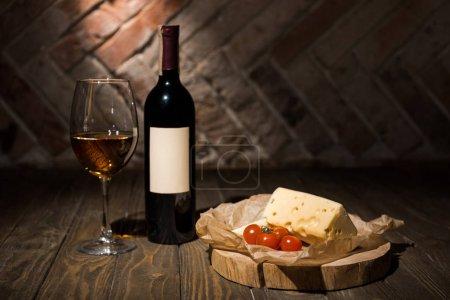 Photo pour Vue rapprochée de la bouteille et du verre de vin avec fromage et tomates cerises sur papier sulfurisé sur souche décorative en bois - image libre de droit