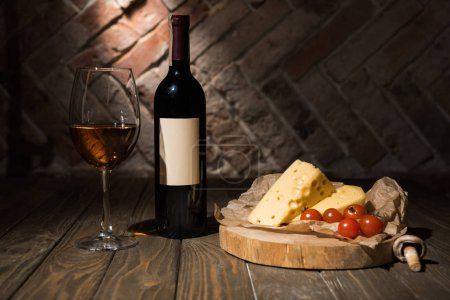 close up view of bottle and glass of wine with cheese and cheery tomatoes on baking paper on wooden decorative stump