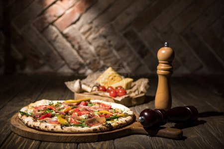 Photo for Selective focus of italian pizza, spices, cherry tomatoes and cheese on wooden tabletop - Royalty Free Image