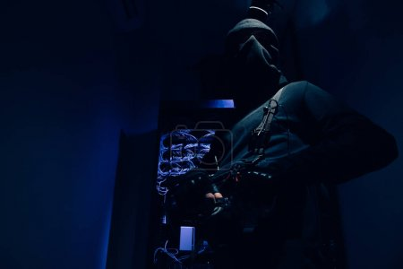 low angle view of hacker in black clothing with various cables on background