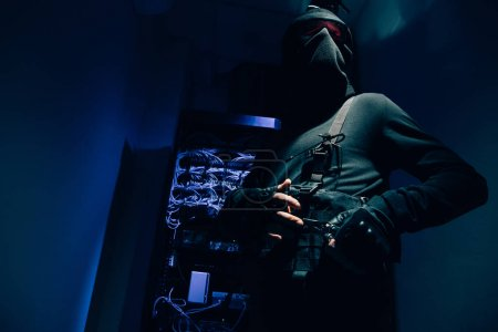 low angle view of hacker in black clothing and eyeglasses with various cables on background