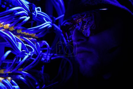 side view of hacker in eyeglasses looking at various wires