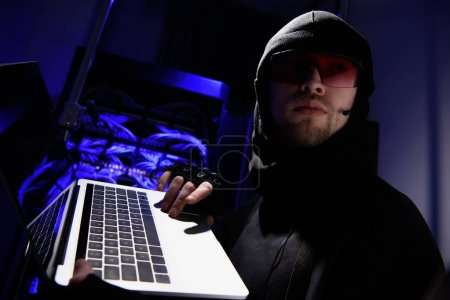 side view of hacker in eyeglasses with laptop looking away with cables on background