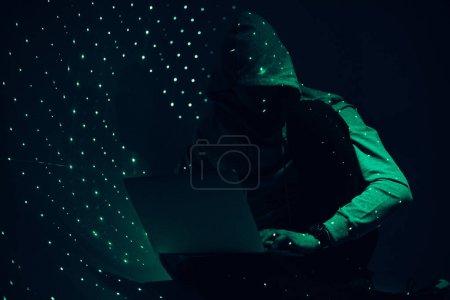 image tonique de la silhouette du pirate dans le sweat à capuche en utilisant un ordinateur portable