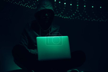 toned picture of silhouette of hacker in hoodie using laptop