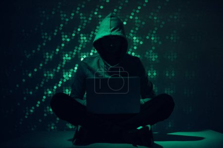 Photo pour Photo tonique de silhouette du hacker en hoodie via ordinateur portable - image libre de droit