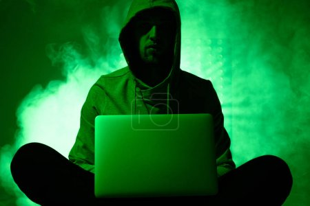 toned picture of hacker in hoodie with laptop