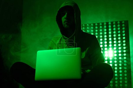 toned picture of male hacker in hoodie with laptop